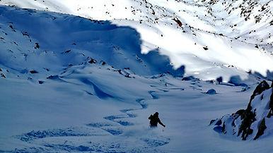un esquiador bajando por nieve virgen con un guia de montaña