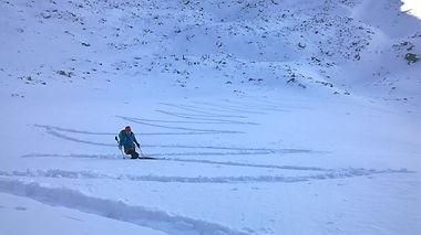 un skieur gravissant des traçes en forme de Z avec un guide de montagne