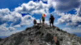 Tres montañeros llegando a la cima del Coma Pedrosa con un guia de montaña