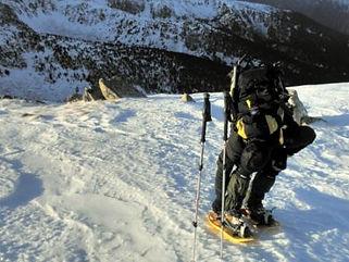 un guia de montaña regulandose las raquetas de nieve para guiar a sus clientes por las montañas nevadas