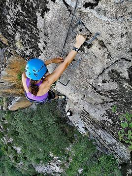 una escalador subiendo la via ferrata del roc d'esquers con un guia de montaña