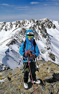 un garçon au sommet du Montmalus avec des skis de randonnée et son guide privé