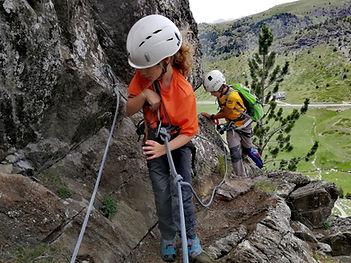 dos niños escalando la via ferrata del clots de l'Aspra con un guia de montaña