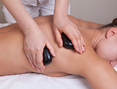 Therapist doing relaxing hot stone massa