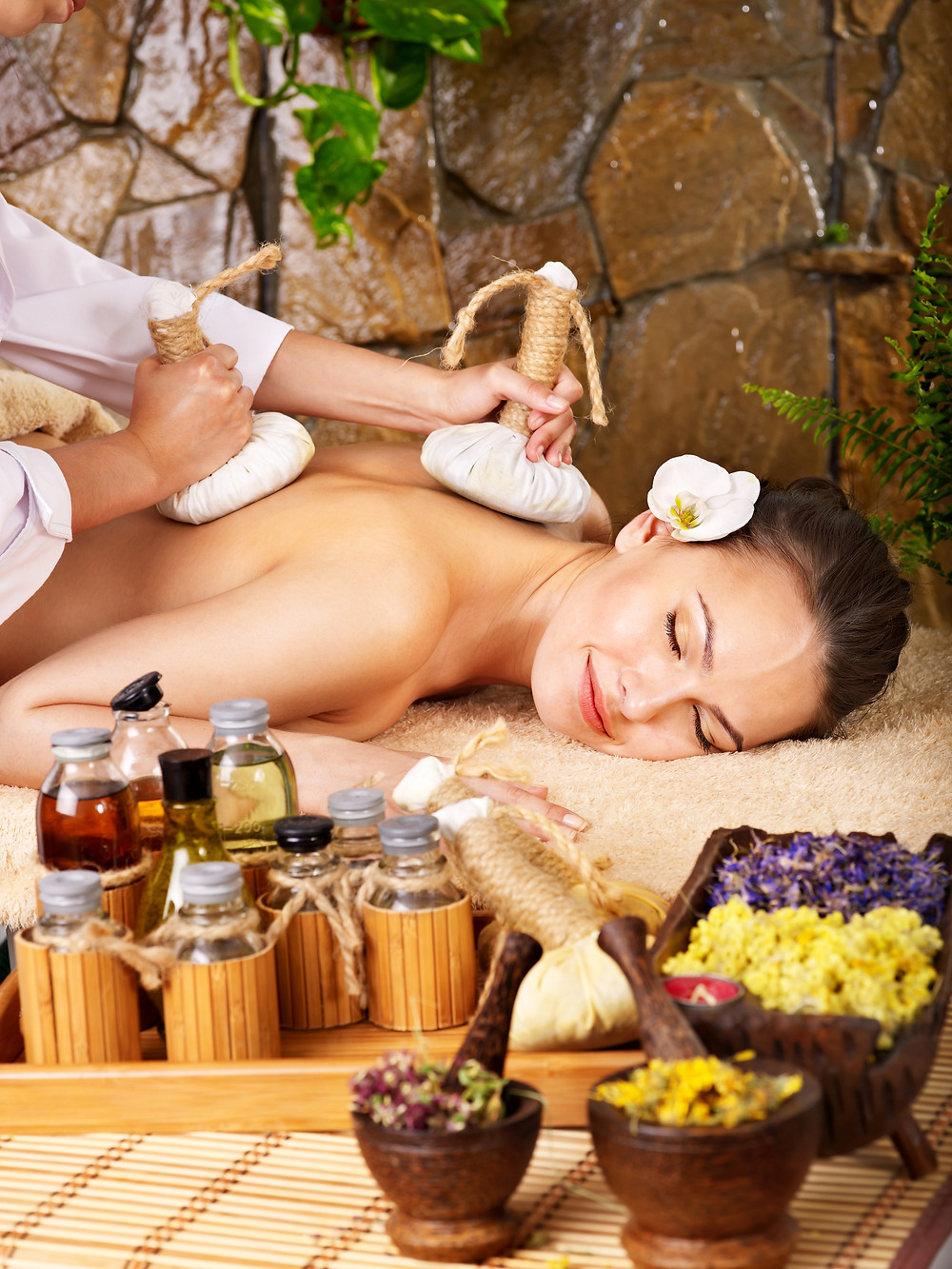 Woman getting thai herbal compress massage in spa..jpg