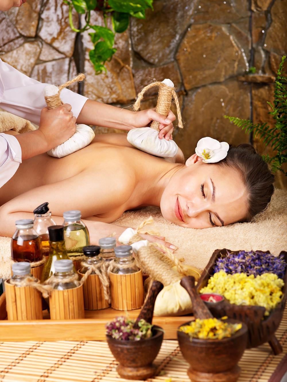 Woman getting thai herbal compress massage in spa..jpg