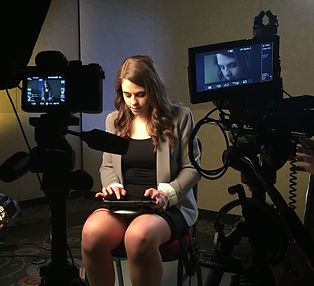 Jordyn, a white female with brown hair, looks down at her iPad. She is surrounded by cameras.