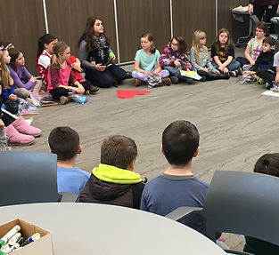Students sit in a circle, as Jordyn leads an activity. There is a big, paper heart in front of her.