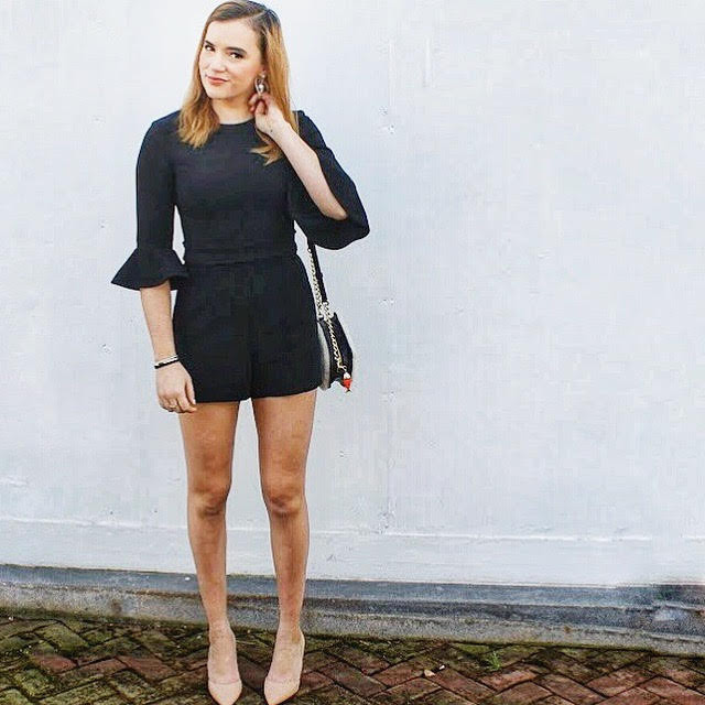 Outfit photo wearing black romper standing against white wall