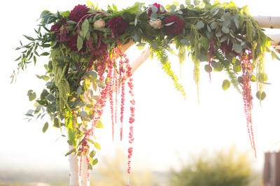 Burgundy and greenery on arch