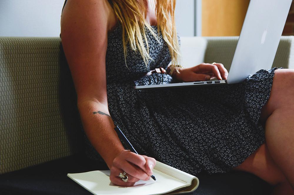 Mulher com laptop no colo fazendo anotações