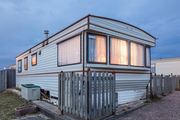 Old vacation home trailer illuminated at
