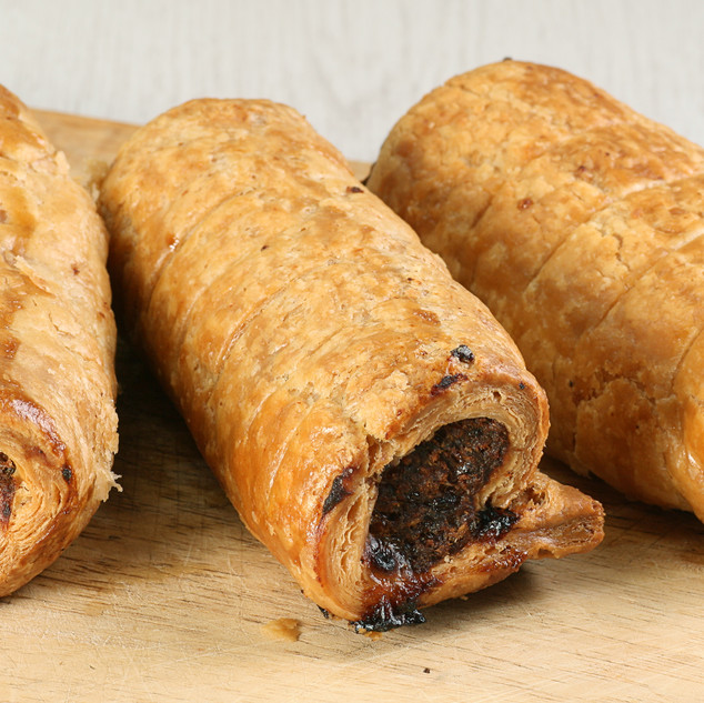hot pastry sausage rolls on a wooden boa