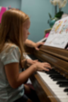 Young girl having piano lessons
