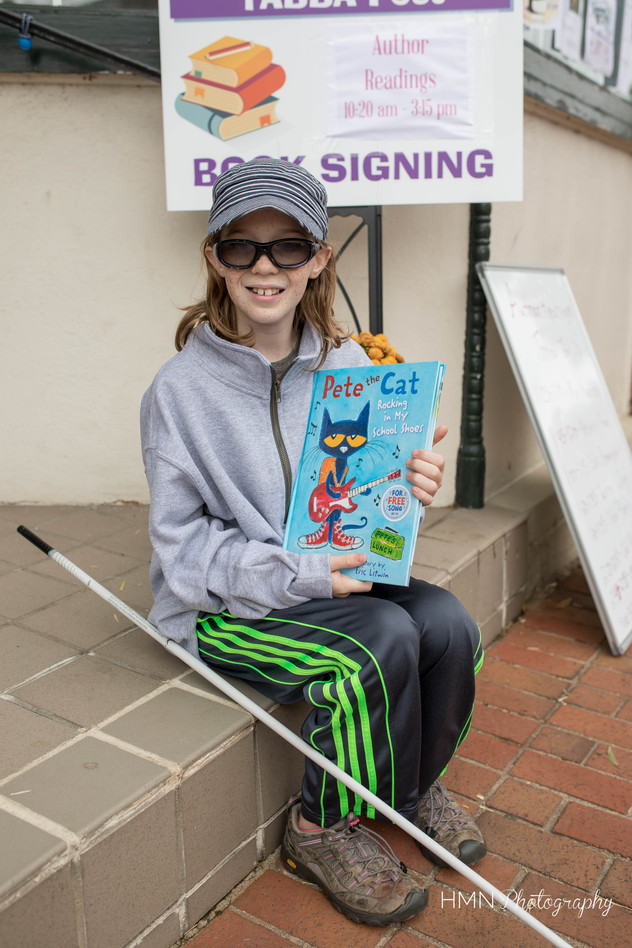 "Blind girl holding braille copy of ""Pete the Cat"" by Eric Litwin"
