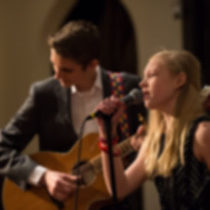 Young female singer and teenage boy guitarist performing