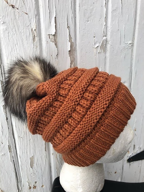 Rust knit hat with Opossum pompom