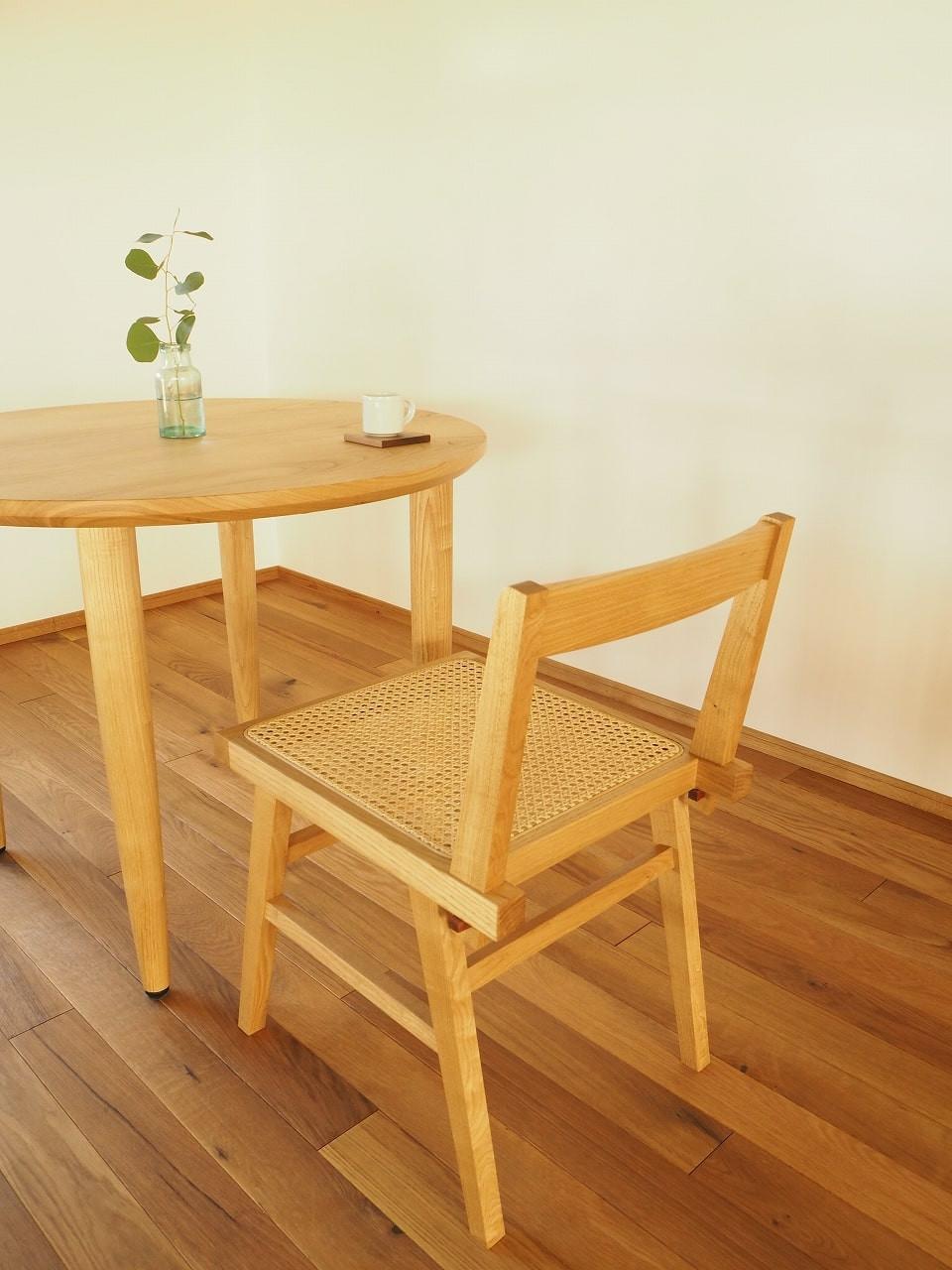 ラウンドテーブルとラタンの椅子の組み合わせ。ともに国産の栗材で製作しています。