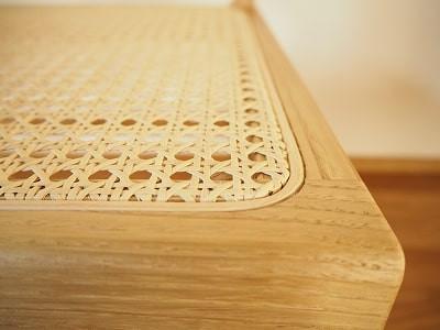 籐シートを周囲の溝にはめ込み、籐芯を打ち込んで固定しています。