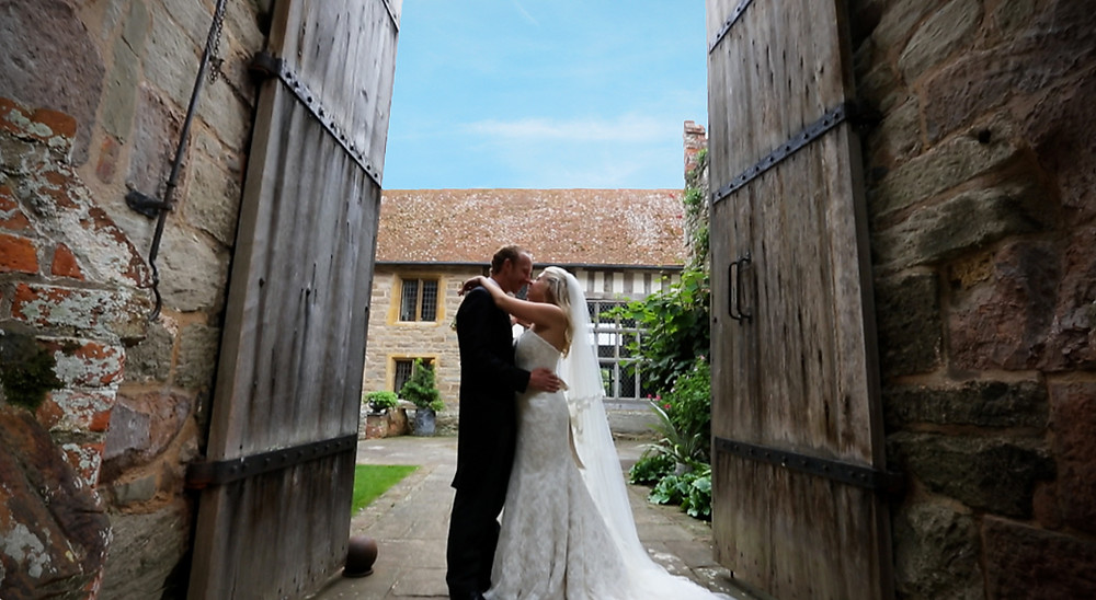 A quiet kiss in the amazing Birtsmorton Court where we are recommended wedding videographers.