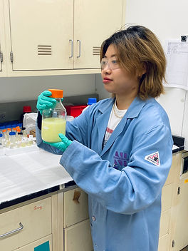 Asian female with short, brown hair, wearing safety goggles and holding a bottle of mirky yellow liquid, looking weary