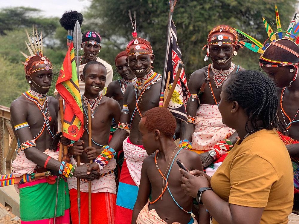 A woman gender specialist smiles with young Samburu warriors