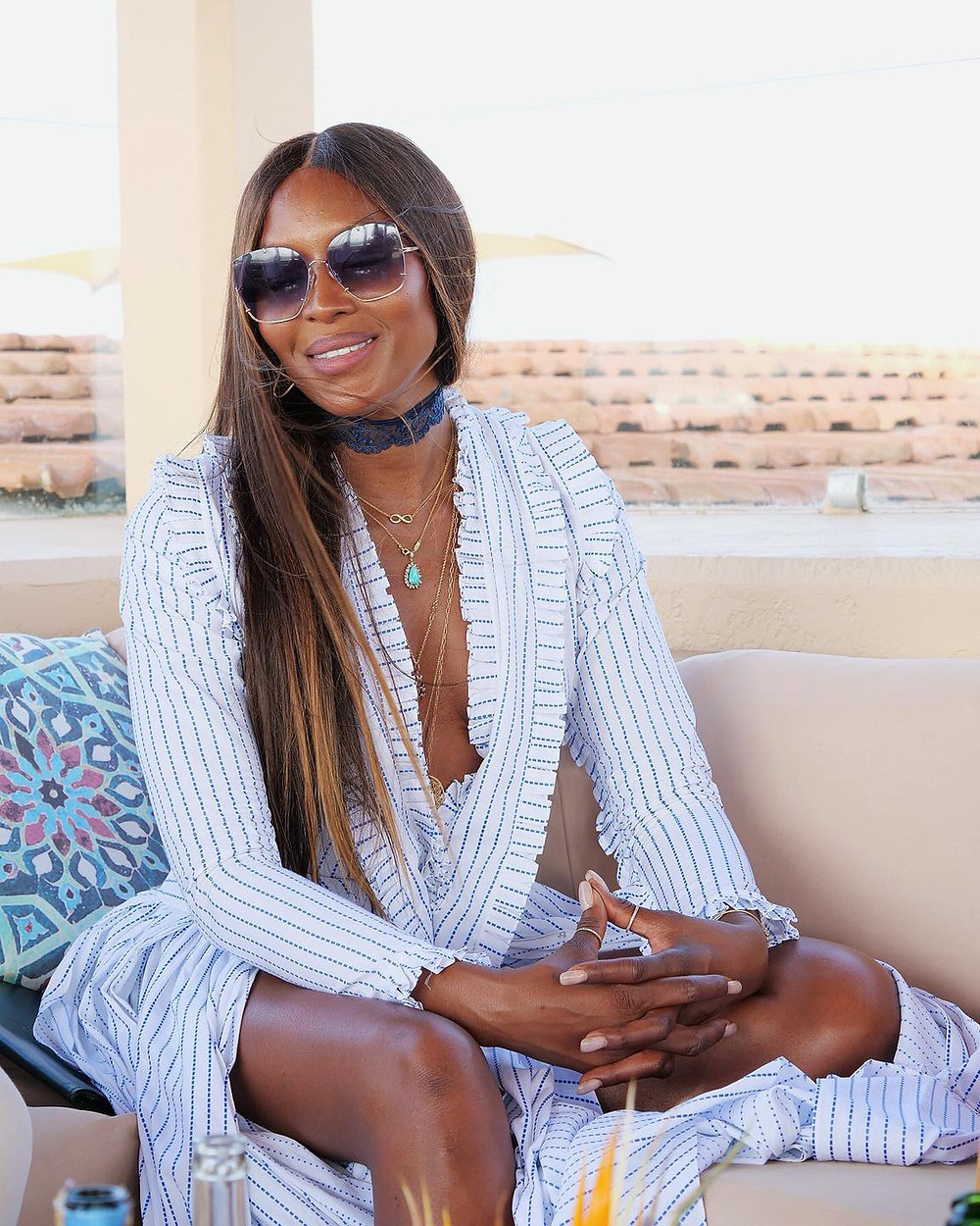 Supermodel Naomi Campbell in Kenya sitting and smiling wearing sunglasses