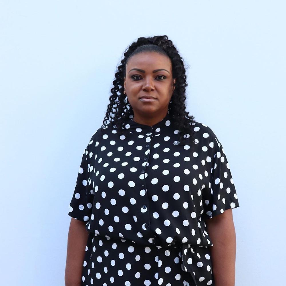 Mulher veste conjunto de poá com fundo preto e bolinhas brancas
