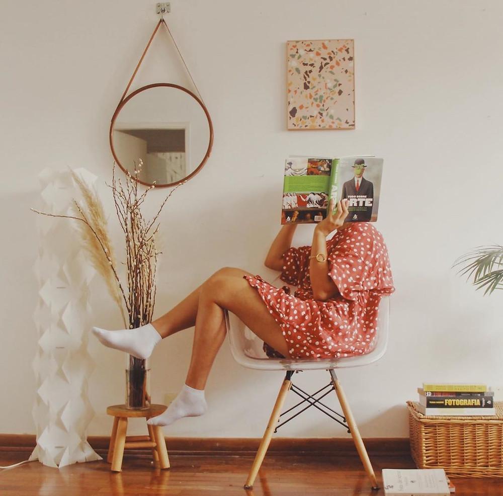 Na foto uma mulher sentada vestindo um macaquinho rosa de bolinhas e segurando uma revista que tampa seu rosto