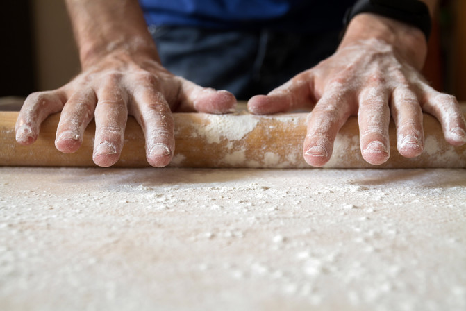 Man's hands are rolling out dough in flo