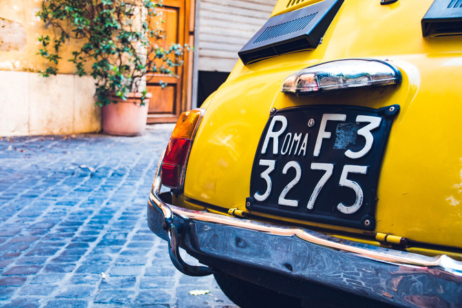 Vintage yellow car in the street with an