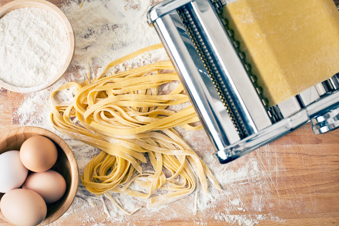 fresh pasta and pasta machine on kitchen