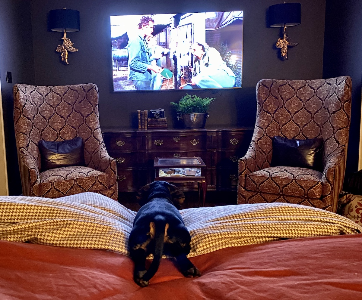 Louie watching an old MASH sitcom in bed with the family.