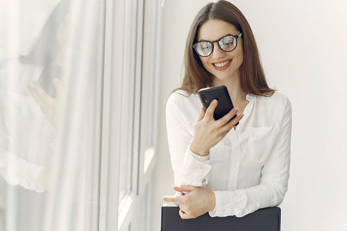 smiling-woman-using-smartphone-in-office