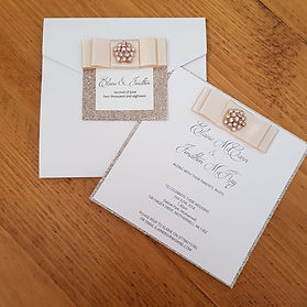 White and gold glitter wedding invitation, with satin ribbon and gold diamante embellishment