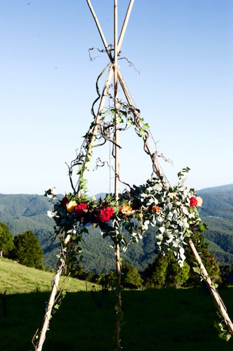 Tall bamboo tripod tipi floral display & ceremony backdrop styled with flowers & foliage by Brisbane florist & event stylist
