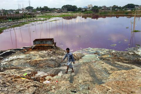 A man walking on the shore of a highly polluted lake ¡.