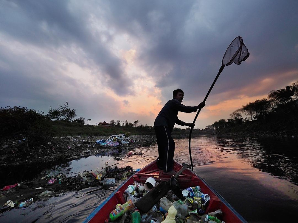 A man pushes his canoe trough a river full of plastic trash
