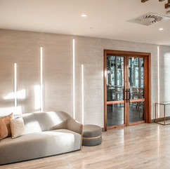 Polished plaster luxury hotel foyer with a couch and led strip lighting on walls displaying the white polished plaster finish
