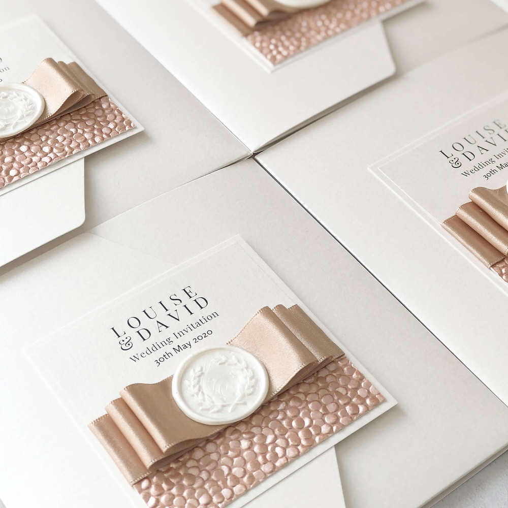 cream rose gold pocketfold wedding invitation with satin bow, pebble paper and wax seal