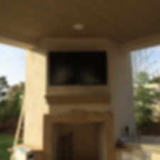 55 in. Sunbrite all weather TV on outdoor fireplace. Equipment in cabinet to the right.