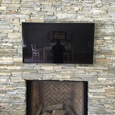 Tv mounted on stone with wires concealed