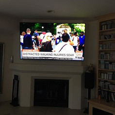 75 inch Samsung Q9 above a fireplace wit