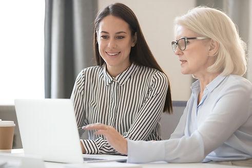 Jobbcoach. Två kvinnor tittar på en dator.
