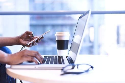 Händer vid en dator och en telefon. Lediga jobb.