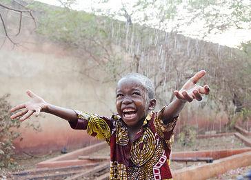 Sweet little African boy under the rain