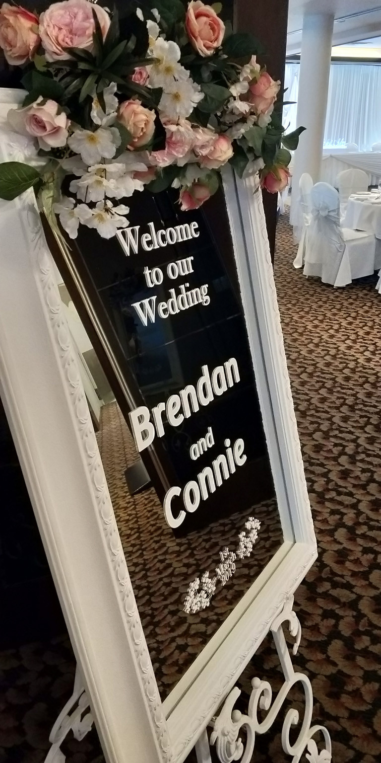 Custom Welcome sign in white writing placed on the white vintage mirror and white wrought iron easel and finished with a mixed pinks silk garland