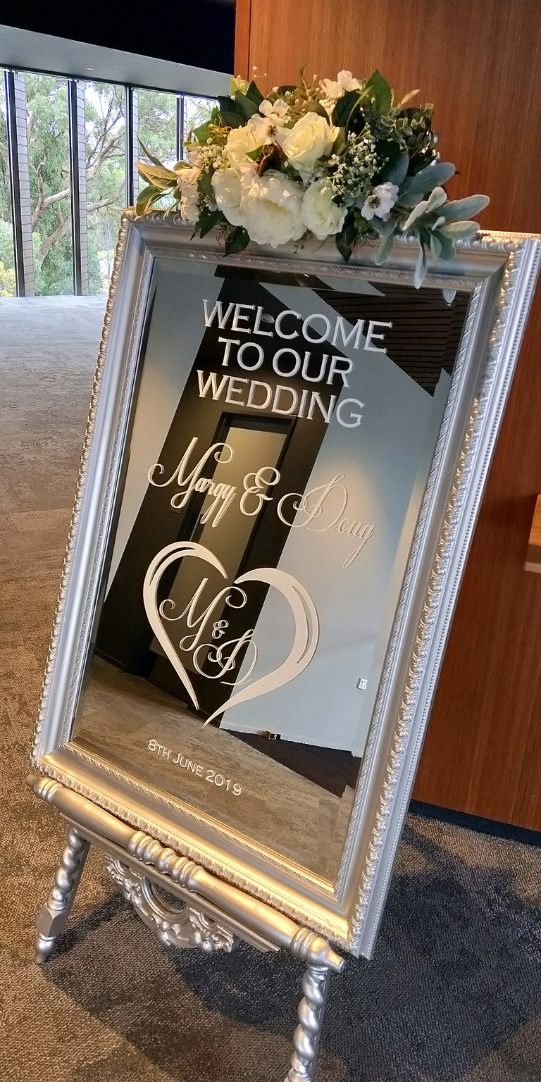 Custom Welcome sign in white writing on the silver Luxe mirror and silver gothic easel for Margy and Doug's wedding