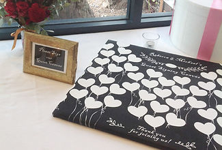 Floating white heart balloons on a black wedding guest signing canvas