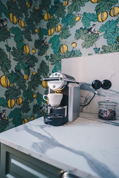 Machine à café sur une table en marbre et papier peint